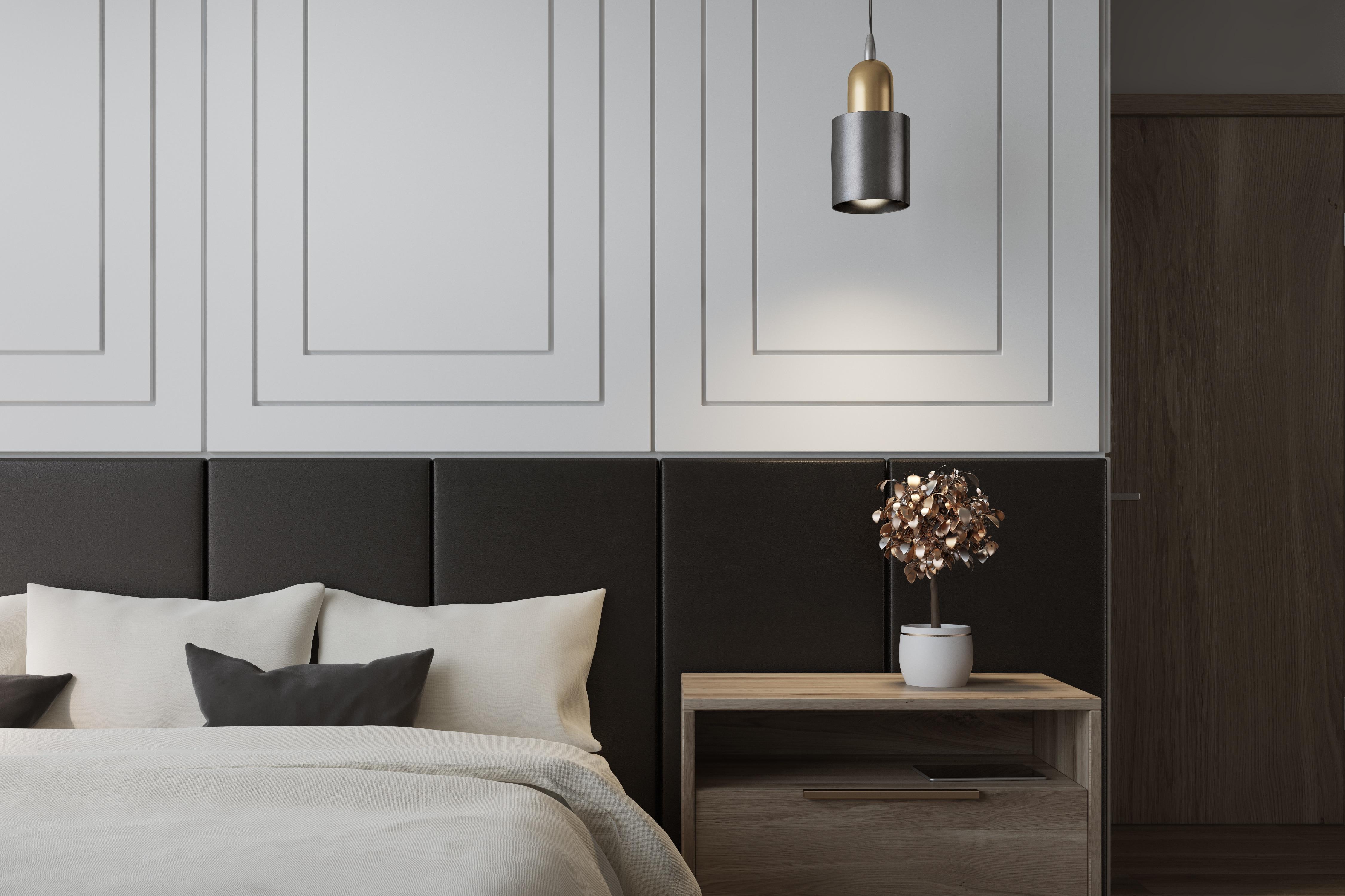 Intérieur d'une chambre blanche avec lit double, draps blancs et table de chevet